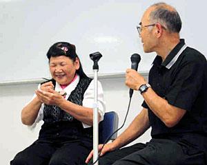 自身の経験を基に手話で講演する梅木久代さん(左)と夫好彦さん=富山市木場町で